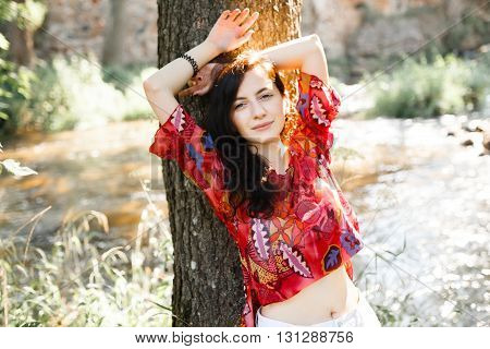 The girl leaning against a tree in a bright dress with chic dark long hair and open emotion in the summer park