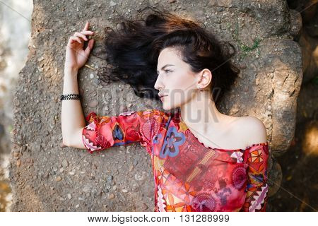 Girl lying and posing on a concrete background in bright clothes with elegant dark long hair and open emotion in the summer park