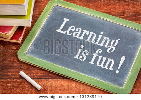 Learning is fun - inspirational text on a  slate blackboard with a white chalk and a stack of books against rustic wooden table