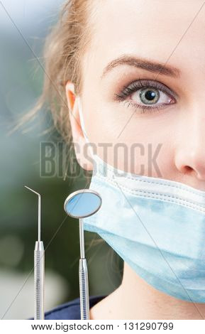 Close-up Of Half Woman Dentist Face Wearing Mask