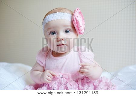 Cute beautiful baby girl sitting on a bed in pink dress.