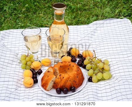Wine fruits and cake on a tablecloth