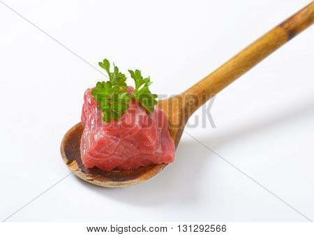 piece of raw beef meat with parsley on wooden spoon