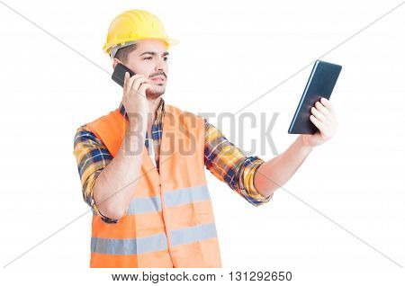 Handsome Engineer Talking On Smartphone And Using A Tablet