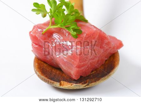 piece of raw beef meat with parsley on wooden spoon - detail