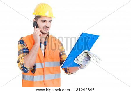 Young Engineer Wearing Helmet With Clipboard Calling On Cellphone