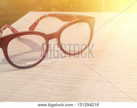 Eye glasses on wood table in the coffee shop under sunlight in the morning with warm / soft color tone