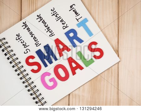 SMART Goals in notebook on wood background (Business Concept)