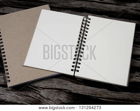 Blank notebook on wood background for take a note (Dark color tone)