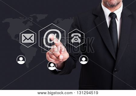 Business man pressing contact us using email digital button on futuristic transparent screen