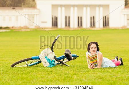Attractive Female Reading A Book Near Vintage Bicycle