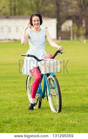 Call me gesture with beautiful smiling female on bicycle relaxing outside in the park