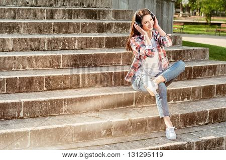Beautiful Hipster Sitting On Stairs In City Park With Earphones