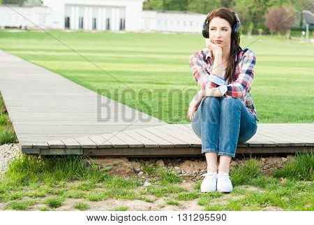 Young Woman Sitting Down On Wooden Pathway With Headphones