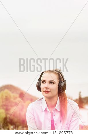 Attractive Young Girl Enjoying Music In A Sunny Day Outside