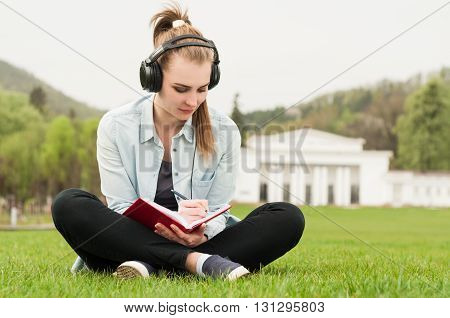 Young Beautiful Female Sitting And Writing Outside With Earphones