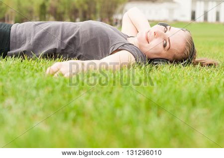Relaxed Female Listening  Music On Earphones Lying On Grass