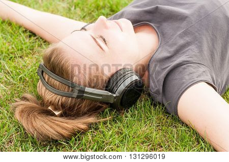 Beautiful Woman In Closeup Lying On Grass And Listen Music