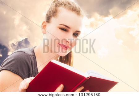 Closeup portrait of attractive woman smiling and winking while reading a book in the park
