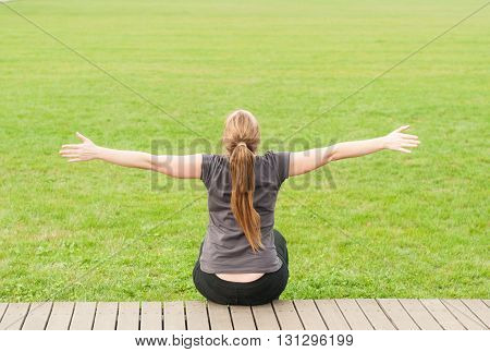 Young Woman Sitting In The Park With Arms Outstretched