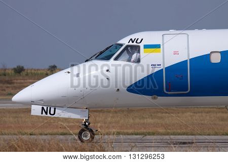 Simferopol Ukraine - September 13 2010: Embraer ERJ-145 regional plane nose part closeup with pilots visible in the cockpit