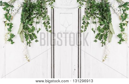 white old wooden door in the room and green branches.