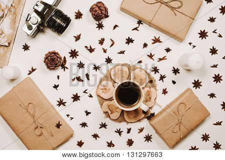 Cup of coffee on wooden stand with star anise, cones, presents in parchment and film camera at white background. Flat lay, top view, overhead view