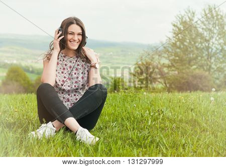 Beautiful Young Female With Earphones Outdoors Enjoying Music