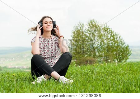Relaxed Woman Listening Music On Headphones Sitting Down On Lawn