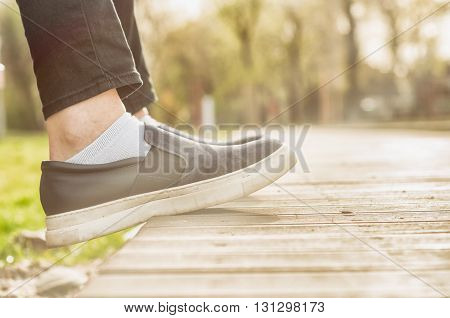Closeup of female's feet wearing casual shoes sitting outside in the park and relaxing