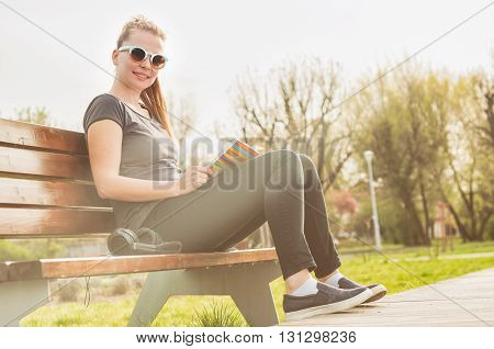 Young happy hipster with glasses enjoying freetime outside with music and a book in sunny day