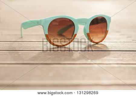 Vintage glasses on wooden desk outside in closeup view as uv rays protection concept