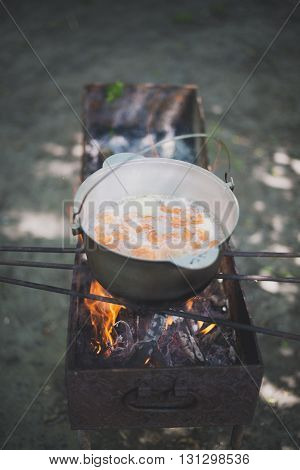 cauldron with fish soup on the grill