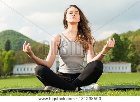 Beautiful Girl Outside In Summer Park Sitting In Lotus Pose