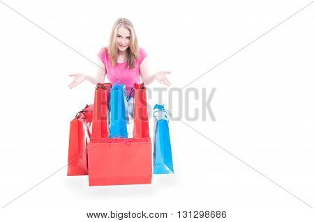 Smiling young woman with colorful shopping bags enjoying sales with copyspace isolated on white background