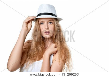 Closeup of beautiful slytish woman posing in fedora hat, over white background