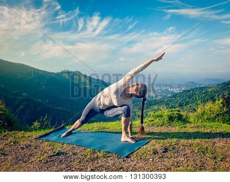 Vintage retro effect hipster style image of sporty fit woman practices yoga asana Utthita Parsvakonasana -  extended side angle pose outdoors in mountains in the  morning