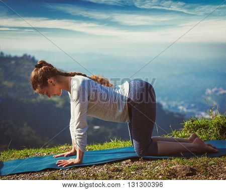 Vintage retro effect hipster style image of sporty fit woman practices yoga asana bitilasana - cow pose outdoors in mountains