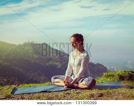 Vintage retro effect hipster style image of sporty fit woman practices yoga asana Baddha Konasana - bound angle pose outdoors in HImalayas mountains in the morning with sky. Himachal Pradesh, India