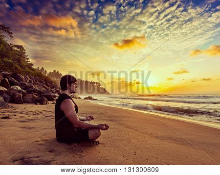Vintage retro effect hipster style image of sporty fit man doing yoga meditating in padmasana lotus pose on tropical beach on sunset