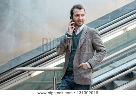 urban man calling on the phone on an escalator