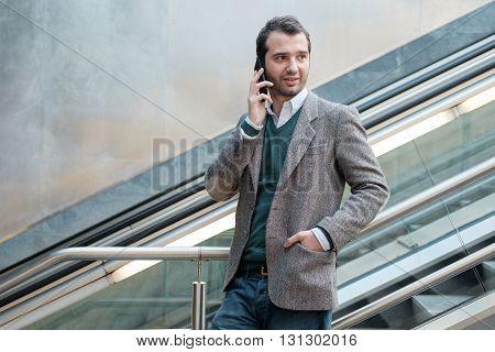 urban man calling on the phone on an escalator
