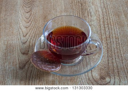 A cup of tea with a chocolate biscuit on a saucer, displayed on a tabletop