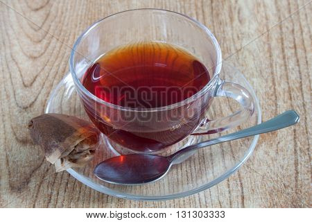 A fresh cup of tea, with a spoon and the used teabag.