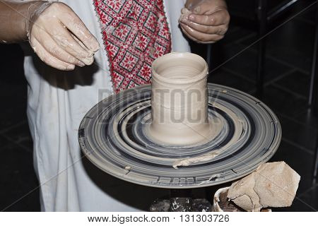 child in an embroidered shirt makes a pitcher on the potter's wheel