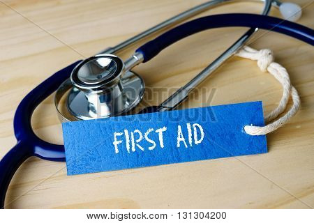 Medical Conceptual Image With First Aid Words And Stethoscope On Wooden Background.