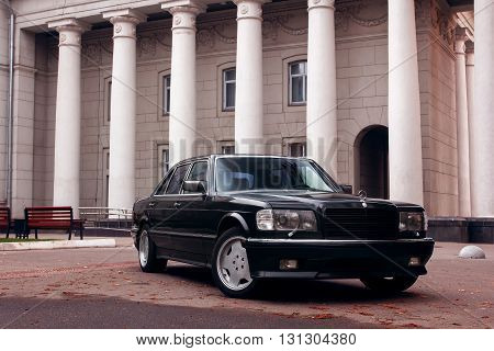 Saratov, Russia - September 28, 2014: Black car Mercedes-Benz near old building with columns at daytime