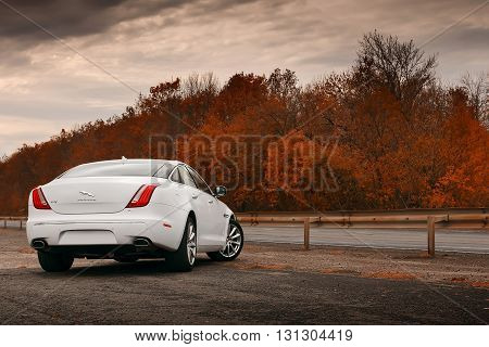 Saratov, Russia - October 16, 2014: Whtie Jaguar XJ car stay on wet asphalt road at daytime