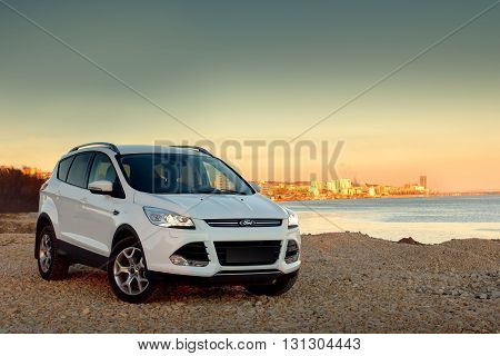 Saratov, Russia - November 25, 2014: White car Ford Kuga fast drive at stone coast at sunset