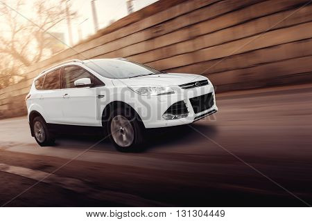 Saratov, Russia - November 25, 2014: White car Ford Kuga fast drive on road in the city at sunset